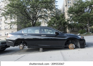 New York, NY, USA August 8, 2014 automobile jacked up on stones with all tires stolen