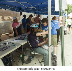 New York, NY USA - August 5, 2017: Volunteers for Department of Transportation help and give away bike helmets during Summer Streets festival along Park Avenue to play, run, walk, bike