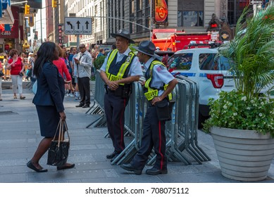 New York, NY USA August 3, 2016 --Pedestrians and public safety officers go about their business in Times Square, New York. Editorial Use Only.