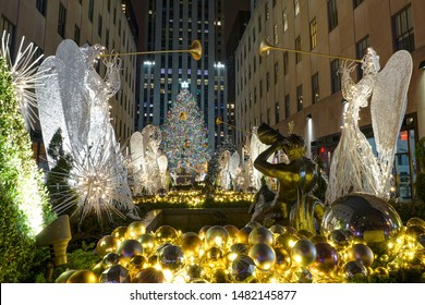 New York, NY, USA - December 28, 2016. A view from the sidewalk of 5th Avenue of the Christmas tree at Rockefeller Center, with angels lining both sides of the garden.
