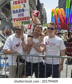 New York, NY USA - June 29, 2014: Gay couple with their daughter attend annual 44th Pride Parade on Fifth Avenue in Manhattan