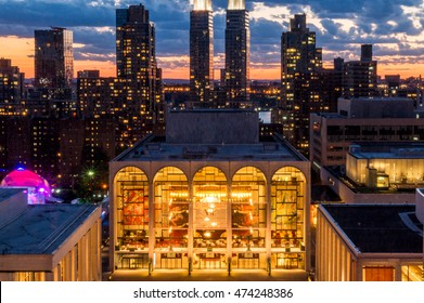 New York, NY, USA - June 22,2016: View of fully lit Metropolitan Opera House, located on the Upper West Side of Manhattan in New York City  with the highrise buildings and sunset in the background.