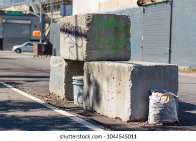 NEW YORK, NY / USA - March 11, 2018: Cement blocks covered in graffiti by the sidewalk.