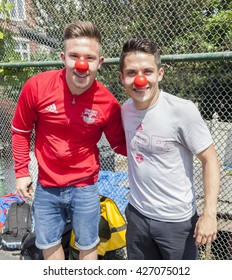New York, NY, USA - May 26, 2016: New York Red Bull players Alex Muyl and Connor Lade celebrate 'Red Nose Day' with kids at the school yard of PS 154, Brooklyn