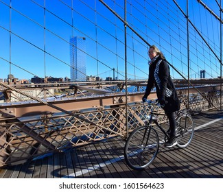 New York, NY, USA - November 30, 2019. New York experience. Cycling on Brooklyn Bridge, pedestrian structure over Hudson river, from Brooklyn to Manhattan.