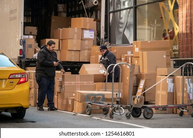 New York, NY/ USA-December 8, 2018 FedEx deliverymen sort a mountain of packages in Soho in New York on Saturday, December 8, 2018 during the Christmas shopping season.