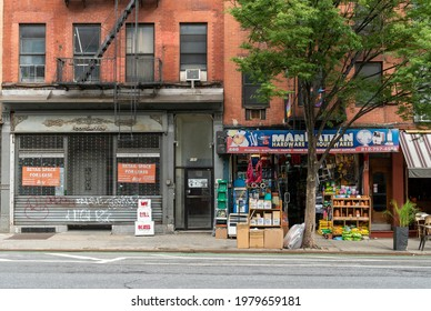 New York NY USA-May 23, 2021 Closed storefront next to a mom and pop dry goods store in the Hells Kitchen neighborhood of New York