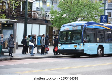 New York, NY/United States- 04/23/2019: People wait for an MTA bus on the curb in Manhattan.