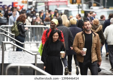 New York, NY/United States- 04/23/2019:A diverse group of people walk down a Manhattan sidewalk holding coffee in the morning