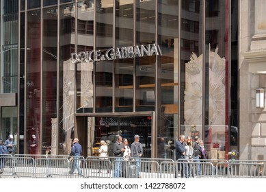 New York, NY/United States- 04/28/2019: A group of people walk past the exterior of Dolce & Gabanna's flagship store on Fifth Avenue in New York