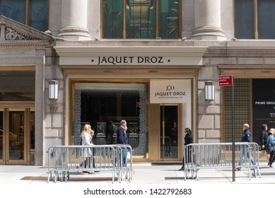 New York, NY/United States- 04/28/2019: Passerby stroll past the Jaquet Droz flagship store on New York's Fifth Avenue.