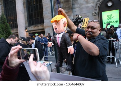 New York, NY/USA- April 14, 2016: A man poses with a hanging Donald Trump pinata. Hundreds of demonstrators protested presidential candidate Donald Trump near Penn Station.