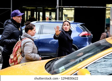 New York, NY/USA.  January 19, 2019: Alexandria Ocasio-Cortez (right) waves goodbye to her fans before entering a cab after the Women's Unity Rally in New York, NY.