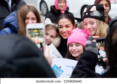 New York, NY/USA.  January 19, 2019: Alexandria Ocasio-Cortez (center) takes photos with fans waiting for a cab after the Women's Unity Rally in New York, NY.
