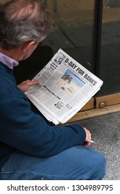 """New York, NY/USA- May 6, 2009: Middle-aged man reading newspaper while smoking. Newspaper headline states """"D-Day For Banks,"""" alluding to consequences arising from financial crisis that began in 2008."""
