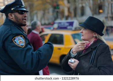 New York, NY/USA- November 11, 2008: A male New York police officer (NYPD) gives directions to a female tourist who is lost.