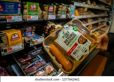 New York NY/USA-April 22, 2019 A shopper chooses a package of Beyond Meat brand Beyond Sausage from a cooler in a supermarket in New York