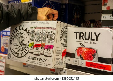 New York NY/USA-May 13, 2019 A discerning consumer chooses a case of White Claw brand hard seltzer among other brands in a cooler in a supermarket
