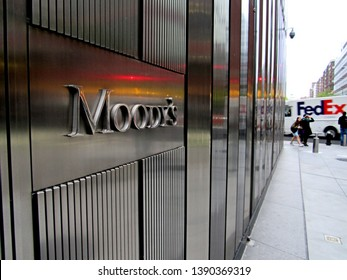 New York, NY/USA-May 3, 2019: The stainless steel facade of 7 World Trade Center and lettering of the Moody's Investor Services sign reflect color from a traffic signal.