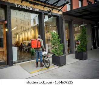 New York NY/USA-October 28, 2018 A DoorDash delivery person outside of a branch of the Sweetgreen restaurant  chain in the Meatpacking District in New York