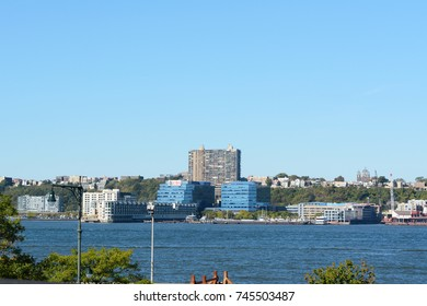 NEW YORK - OCTOBER 20, 2017: View across the Hudson River to New Jersey, to Weehawken Cove and Lincoln Harbor. Numerous other buildings line the river bank and skyline on a sunny day.