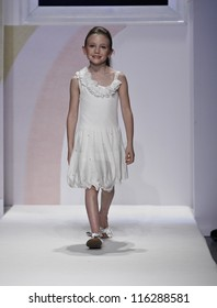 NEW YORK - OCTOBER 21: Girl walks runway for petite Parade show by Miss Blumarine during kids fashion week sponsored by Vogue Bambini & Swarovski Elements at Industria Supertudio on Oct 21 2012 in NYC