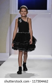 NEW YORK - OCTOBER 21: Girl walks runway petite Parade by Ooh! La, La! Couture during kids fashion week sponsored by Vogue Bambini, Swarovski Elements at Industria Superstudio on Oct 20, 2012 in NYC
