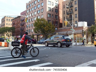 NEW YORK - OCTOBER 23, 2017: Delivery cyclist wearing high visibility tabard waits at intersection of West 44th Street and 10th Avenue. Construction worker holds a SLOW warning sign for traffic.