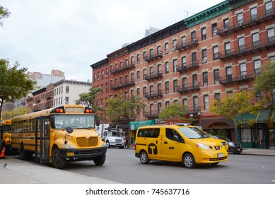 NEW YORK - OCTOBER 23, 2017: Yellow school bus and NYC taxi cab on 10th Avenue in Manhattan. Both are iconic American vehicles seen on the city streets.