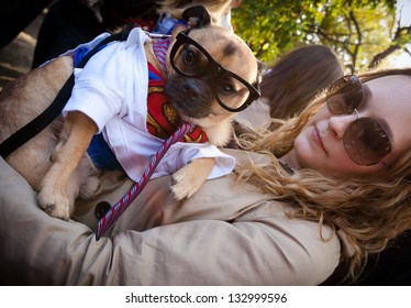 NEW YORK - OCTOBER 24, 2010: An unidentified young woman holds her dog, dressed as the character Clark Kent, for the annual Tompkins Square Halloween Dog Parade.