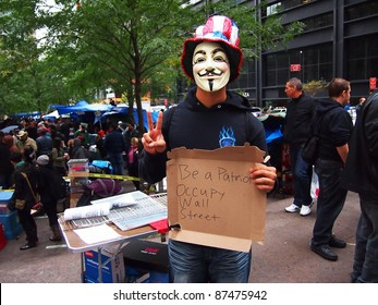 "NEW YORK - OCTOBER 26: An unidentified protester in a Guy Fawkes mask holds up an ""Occupy Wall Street"" sign, October 26, 2011 in New York City, NY. The demonstration began in Zuccotti Park on September 17, 2011."