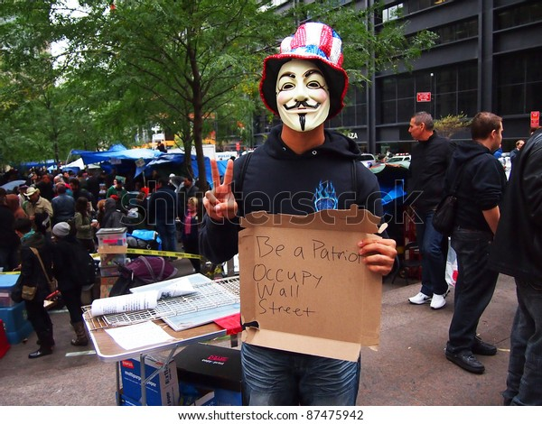 """NEW YORK - OCTOBER 26: An unidentified protester in a Guy Fawkes mask holds up an """"Occupy Wall Street"""" sign, October 26, 2011 in New York City, NY. The demonstration began in Zuccotti Park on September 17, 2011."""