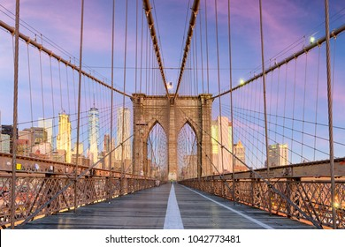 New York, New York on the Brooklyn Bridge Promenade facing Manhattan's skyline at dawn.