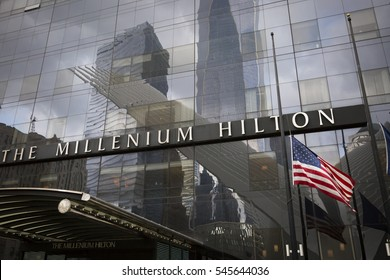 NEW YORK - SEPT 11 2016: American Flag at half mast at the Millenium Hilton Hotel with the Freedom Tower and WTC site reflection on the windows on the 15th anniversary of the Sept 11 terror attacks.
