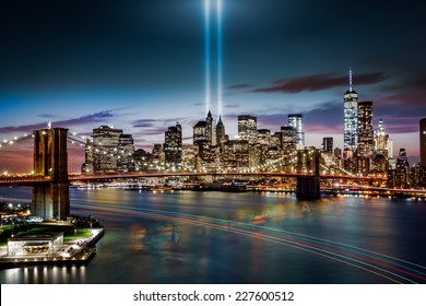 NEW YORK - SEPTEMBER 11, 2014: Tribute in Light memorial, Brooklyn Bridge and the Lower Manhattan skyline at dusk. A boat leaves colorful light trails on the Hudson River.