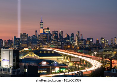 New York, New York - September 11, 2020 : The 9/11 tribute lights seen next to One World Trade at sunset, with car light trails from Interstate 278 (I-278) heading towards Manhattan.