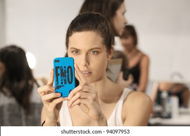 NEW YORK - SEPTEMBER 13: Model holds iPhone with Fashion Night Out case backstage during Spring/Summer 2012 during Mercedes-Benz Fashion Week on September 13, 2011 in New York.