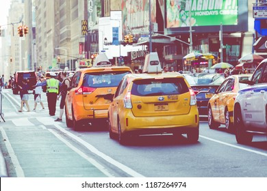 NEW YORK - SEPTEMBER 2, 2018: Yellow cab speeds through Times Square the busy tourist intersection of neon art and commerce and is an iconic street of New York City, USA.
