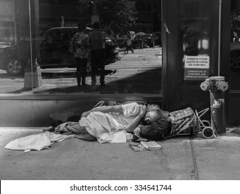 New York - SEPTEMBER 20: A homeless man sleeping on the street of New York on September 20 2015, next to him is his book.