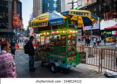 New york, New York - September, 2019: Food stand in Times Square Manhattan New Your City that sells certified Halal food. A black customer is looking at the food pictures