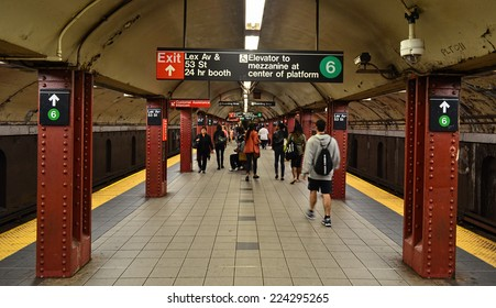 NEW YORK - SEPTEMBER 21, 2014: MTA subway train station platform with people traveling in New York. The NYC Subway is a rapid transit/transportation system in the City of NY.