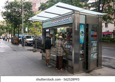 New York, September 28, 2016: Two people are making purchases at a newsstand on Upper West Side in Manhattan.