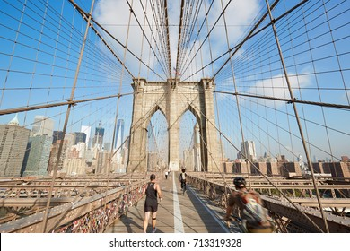 NEW YORK - SEPTEMBER 8: Brooklyn Bridge in a sunny morning with people running and cycling on September 8, 2016 in New York. It is an old bridge completed in 1883.