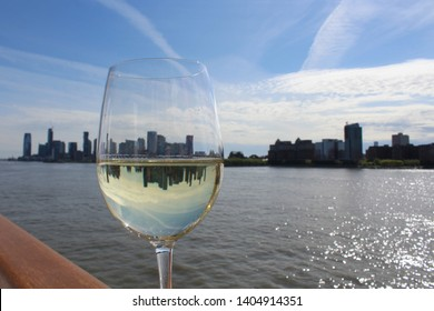 New York skyline reflected in glass goblet of white wine on ship railing in early evening. Setting sunlight sparkles on water. Mirror image of skyline in wineglass.