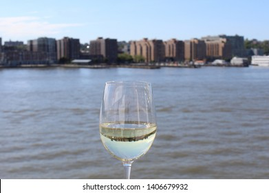 New York skyline reflected in glass crystal stemware goblet of white wine in early evening. Mirror image of skyline in wineglass.