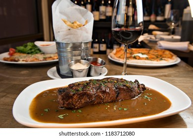 New York Strip au Poivre served with a side of french fries and red wine