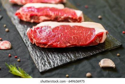 New york strip porterhouse steak meat with spices and herbs against black background
