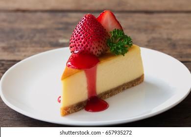 New York style Cheesecake on white plate decorated with fresh strawberry, parsley and strawberry sauce on wood table with copy space so sweet and delicious. Homemade bakery concept.