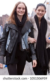 New York, New York / United States - 02 12 2011: Mixed race friendship. Fashion models Nimue Smit and Ming Xi street style