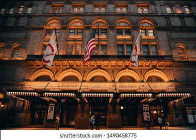 New York, New York - United States of America - July 28, 2019: Carnegie Hall lit with a warm glow at night as New York commuters walk under the flags hanging out front.